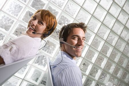 glass block: Businessman and woman wearing headsets sitting back to back by glass block wall, smiling, portrait (tilt) LANG_EVOIMAGES