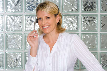 glass block: Businesswoman wearing headset by glass block wall, smiling, portrait, close-up