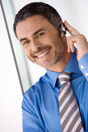 handsfree device: Businessman wearing mobile phone hands-free device, smiling, close-up, portrait (tilt)