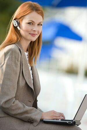 handsfree device: Businesswoman with mobile phone hands-free device using laptop, smiling, side view, portrait