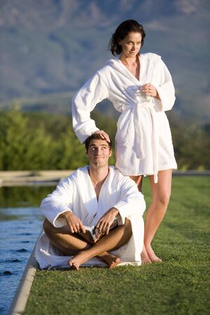 bath robes: Young couple wearing white bath robes outdoors by pool, smiling, portrait