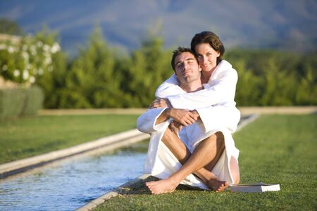 bath robes: Young couple wearing white bath robes embracing outdoors by pool, smiling, portrait LANG_EVOIMAGES
