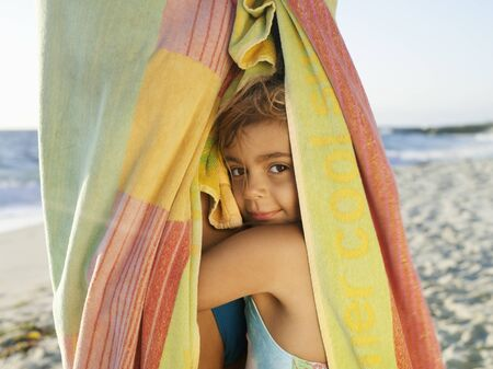 snuggling: Girl (5-7) snuggling up to mother wrapped in large towel on sandy beach, smiling, close-up, side view, portrait LANG_EVOIMAGES