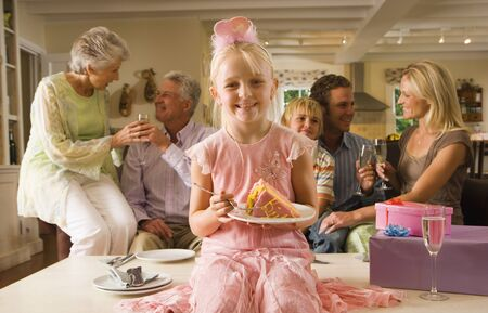lap of luxury: Three generation family sitting on sofa at home, girl (4-6) sitting on coffee table with slice of birthday cake in foreground, smiling, front view, portrait