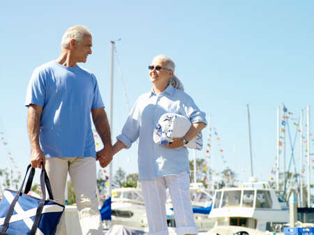 ice chest: Senior couple hand in hand on jetty, smiling at each other, low angle view