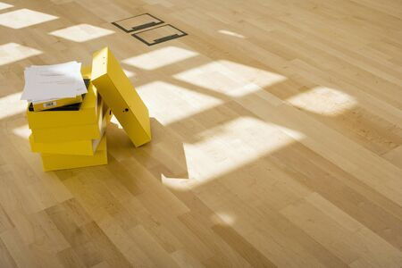 five objects: Documents on stack of yellow folders on office floor, sunlight shining through window LANG_EVOIMAGES