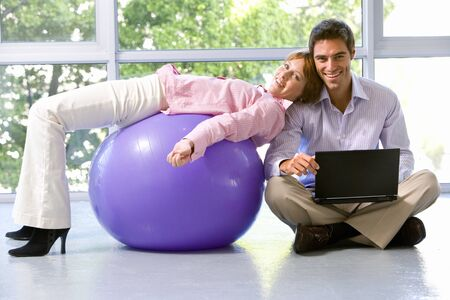 out of context: Businessman with laptop computer on floor in exercise studio by colleague on exercise ball, smiling, portrait LANG_EVOIMAGES