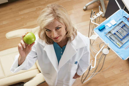 one mid adult woman only: Female dentist holding green apple in dental surgery, smiling, portrait, overhead view