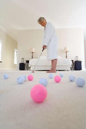 putt: Senior woman standing in bedroom practising golf putt, smiling, portrait, golf balls in foreground