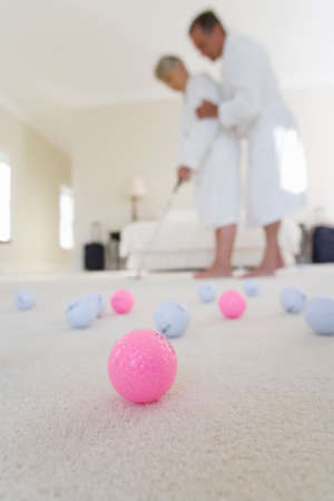 putt: Senior couple in bedroom practising golf putt, focus on golf balls in foreground