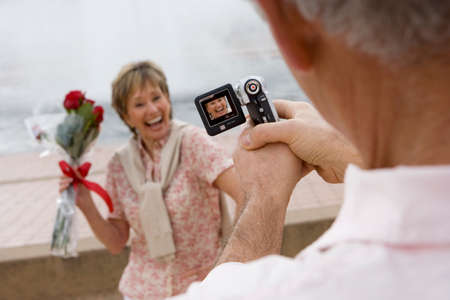 differential focus: Senior woman standing beside fountain, holding bouquet of red roses, smiling, man filming her with portable video recorder (tilt, differential focus)