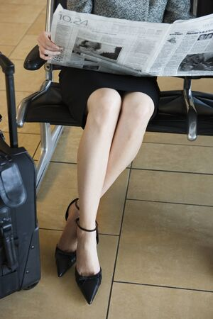low section view: Businesswoman waiting in airport departure lounge, reading newspaper, low section, front view