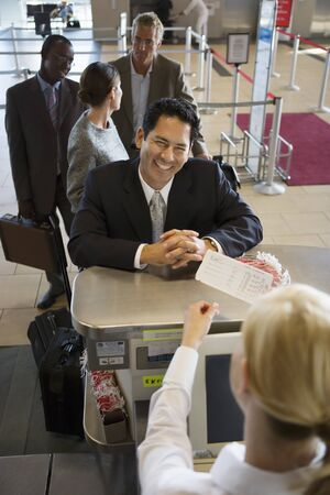 elevated view: Businessman standing at airport check-in counter, smiling, female attendant looking at ticket, elevated view