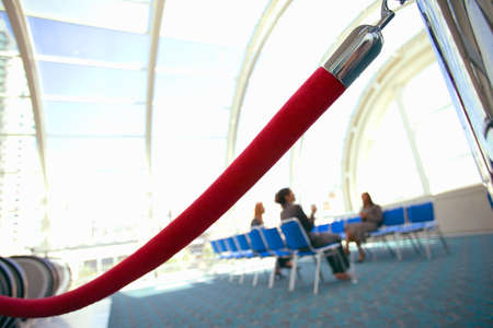 rope barrier: Business people sitting in airport departure lounge, focus on rope barrier in foreground (tilt)