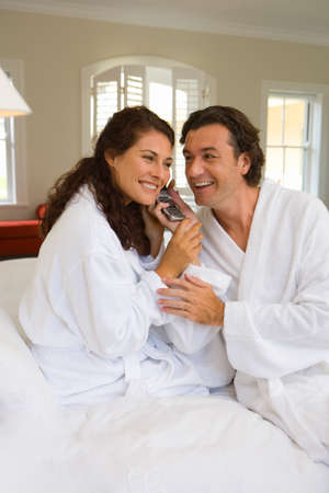 bath robes: Couple wearing white bath robes on bed, both holding telephone receiver, smiling