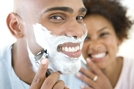 shave: Young woman smiling at man shaving, portrait of man, close-up LANG_EVOIMAGES
