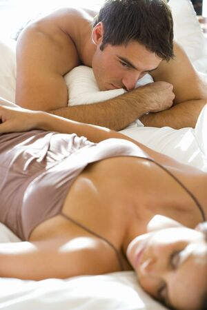 lovemaking: Young man looking at young woman lying on bed asleep