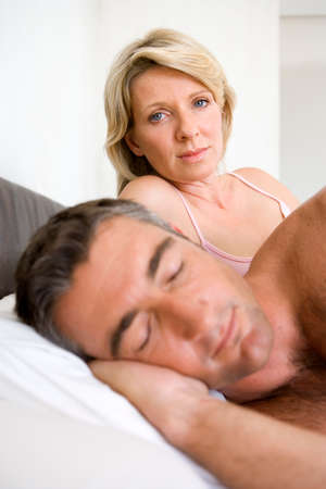 angst: Couple on bed, man asleep in foreground, portrait of woman in background LANG_EVOIMAGES