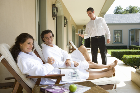 bath robes: Couple wearing white bath robes on deck chairs, man smiling at woman holding magazine, waiter standing in background LANG_EVOIMAGES