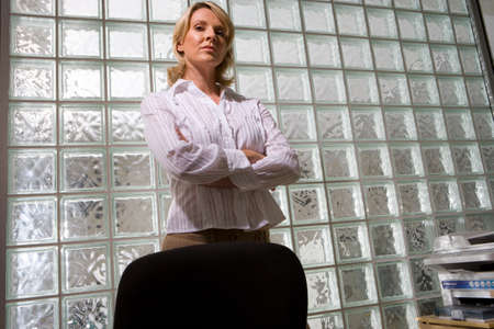 one mid adult woman only: Businesswoman with arms crossed by glass block wall, portrait, low angle view