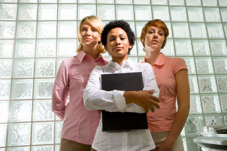 glass block: Three businesswomen standing by glass block wall, one holding book, portrait, low angle view LANG_EVOIMAGES