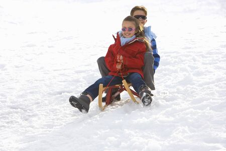to steer a sledge: Boy and girl (7-9) riding sled down snow slope, smiling, low angle view