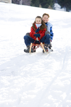 to steer a sledge: Boy and girl (7-9) riding sled down snow slope, smiling, portrait, low angle view