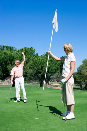 putt: Mature couple playing golf, man punching air in delight at successful putt, woman holding flag on putting green