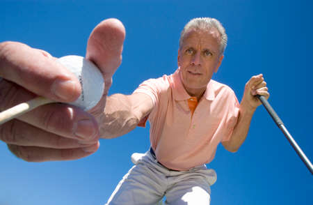 by placing: Mature man placing golf tee in grass on golf course, holding golf ball and club, close-up, upward view (wide angle) LANG_EVOIMAGES