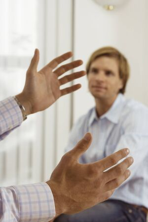 two person only: Two businessmen talking in office, focus on man gesturing with hands in foreground