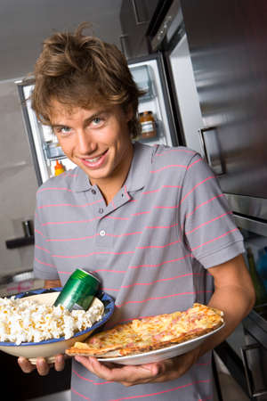 only one teenage boy: Young man holding popcorn and pizza, smiling, portrait, close-up LANG_EVOIMAGES