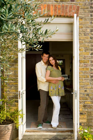 two people fertility: Young man embracing young pregnant woman in doorway, smiling, portrait LANG_EVOIMAGES