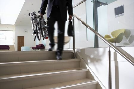 low section view: Businessman carrying commuter bicycle up steps in lobby, low section, rear view (blurred motion)