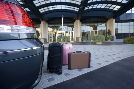 car parking: Luggage beside parked car outside hotel