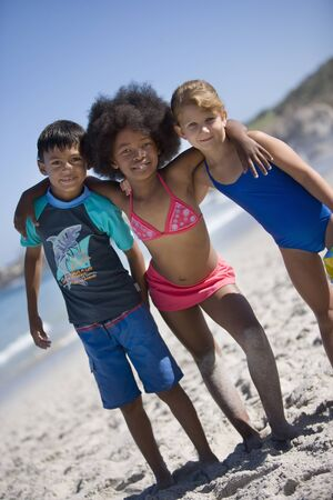 tilt view: Three children (6-10) standing side by side on beach, smiling, front view, portrait (tilt)