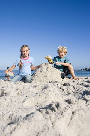 sandcastles: Boy (4-6) and girl (6-8) building sandcastles on sandy beach, smiling, front view, portrait LANG_EVOIMAGES