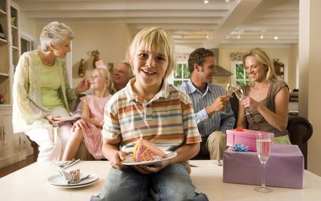 lap of luxury: Three generation family sitting on sofa at home, boy (4-6) sitting on coffee table with slice of birthday cake in foreground, smiling, front view, portrait LANG_EVOIMAGES
