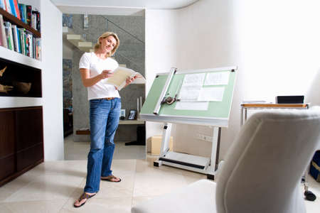 only mid adult women: Woman standing by blue prints on drafting board in home office, smiling LANG_EVOIMAGES