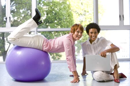 out of context: Businesswoman with laptop computer on floor in exercise studio by colleague on exercise ball, smiling, portrait