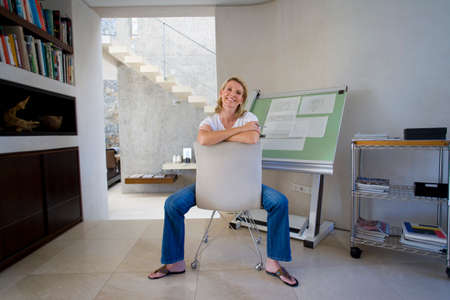 only mid adult women: Woman sitting by blue prints on drafting board in home office, smiling portrait