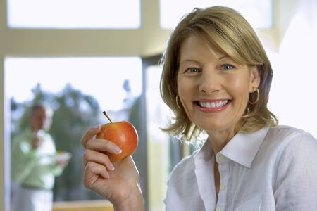 fortysomething: Mature woman eating apple at home, senior man in background, focus on woman, smiling, side view, portrait
