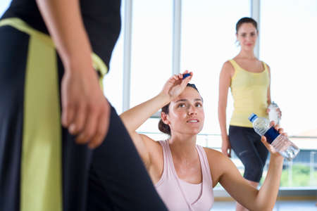 three people only: Woman with water bottle in studio in gym, wiping forehead