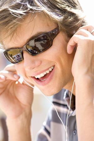 only one teenage boy: Teenage boy (16-18) wearing sunglasses and earphones, smiling, close-up