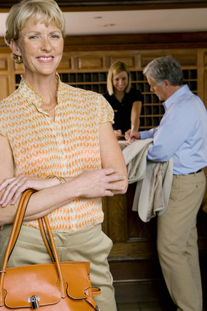 checking in: Mature man checking in at hotel reception desk, female receptionist looking on, focus on mature woman standing in foyer in foreground, smiling, portrait LANG_EVOIMAGES
