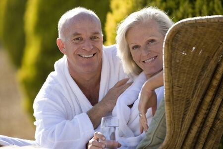 bath robes: Mature couple wearing white bath robes outdoors, smiling, portrait