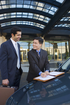two people only: Two businessmen standing beside car outside hotel, man signing contract, smiling