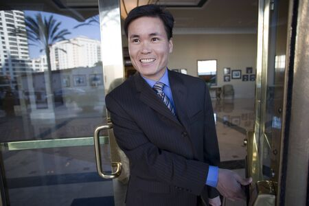 exiting: Businessman opening door, exiting building lobby, smiling