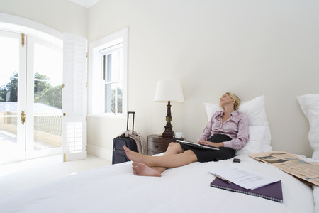 Älteres Geschäftsfrau sitzt auf dem Bett mit Laptop, der heraus Fenster schaut