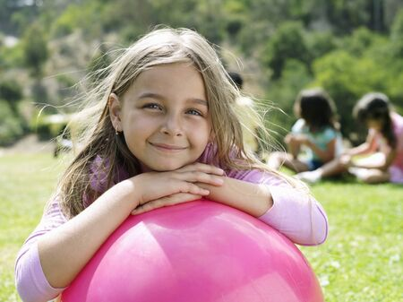 hopper: Girl (7-9) leaning on pink space hopper in park, smiling, portrait, focus on foreground