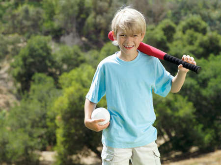 softball: Blonde boy (7-9) standing in park with softball bat and ball, smiling, front view, portrait